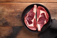 Two fresh raw marble meat, black Angus ribeye steak with spices in iron pan on a old rustic table. Raw beef on a wooden background. Top view with copy space Royalty Free Stock Photos
