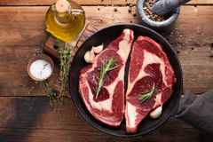 Two fresh raw marble meat, black Angus ribeye steak with spices in iron pan on a old rustic table. Raw beef on a wooden background. Top view with copy space Stock Photo