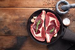 Two fresh raw marble meat, black Angus ribeye steak with spices in iron pan on a old rustic table. Raw beef on a wooden. Background. Top view with copy space Stock Photo
