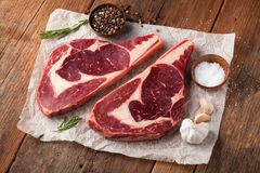 Two fresh raw marble meat, black Angus ribeye steak with spices on a old rustic table. Raw beef on a wooden background.  Stock Photography