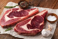 Two fresh raw marble meat, black Angus ribeye steak with spices on a old rustic table. Raw beef on a wooden background.  Stock Photos