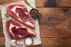 Two fresh raw marble meat, black Angus ribeye steak with spices on a old rustic table. Raw beef on a wooden background. Top view w. Ith copy space Royalty Free Stock Images
