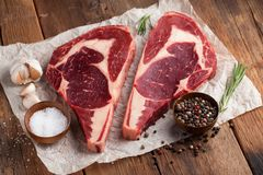 Two fresh raw marble meat, black Angus ribeye steak with spices on a old rustic table. Raw beef on a wooden background. Top view.  Royalty Free Stock Photo