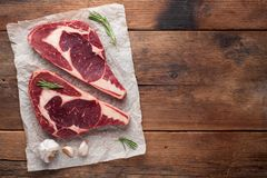 Two fresh raw marble meat, black Angus ribeye steak with spices on a old rustic table. Raw beef on a wooden background. Top view w. Ith copy space Stock Photography