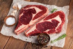 Two fresh raw marble meat, black Angus ribeye steak with spices on a old rustic table. Raw beef on a wooden background. Top view with copy space Stock Photos