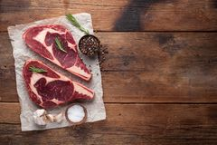 Two fresh raw marble meat, black Angus ribeye steak with spices on a old rustic table. Raw beef on a wooden background. Top view with copy space Stock Photography