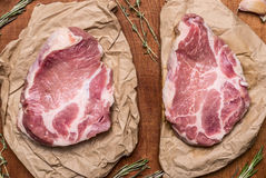 Two Fresh raw pork steak on paper with herbs  wooden rustic background close up top view. Two Fresh raw pork steak on paper with herbs  on wooden rustic Royalty Free Stock Image