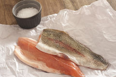Two fresh raw rainbow trout fillets. Displayed flesh side up and skin side up on a piece of crumpled white paper in a kitchen ready to prepare a tasty seafood Stock Photo