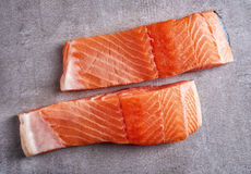 Two fresh raw red salmon fillets. Two fresh raw salmon fillet on grey table, top view Stock Images