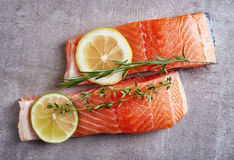 Two fresh raw salmon fillet with lime, lemon and spices Stock Photos
