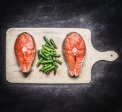 Two fresh raw salmon steak with green beans on cutting board top view. Two fresh raw salmon steak with green beans on a cutting board top view Stock Image