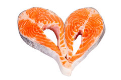A heart made of two raw salmon steaks, isolated on. Two fresh raw salmon steaks having a heart shape are isolated on white Royalty Free Stock Images