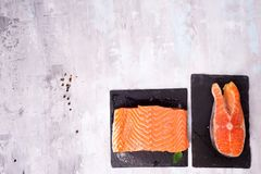 Two fresh raw salmon steaks are laying on the dark slate board. Two fresh raw salmon steaks are laying on the dark slate cutting board. Lean proteins Stock Images