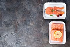 Two fresh raw salmon steaks are laying on white food tray made from polystyrene foam. On stone background. Lean proteins. Flat lay with copy space Royalty Free Stock Photography