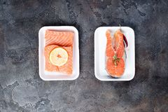 Two fresh raw salmon steaks are laying on white food tray made from polystyrene foam. On stone background. Lean proteins Stock Image