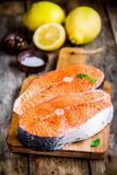 Two fresh raw salmon steaks with lemons closeup. On wooden cutting board Stock Images
