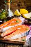 Two fresh raw salmon steaks with lemons and olive oil Royalty Free Stock Photos
