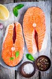 Two fresh raw salmon steaks on paper with salt, peppers, lemon, and basil. On the rustic wooden table Royalty Free Stock Images