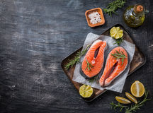 Two fresh raw salmon steaks. On paper with salt, peppers, lemon, and rosemary on black background, top view Stock Images