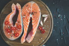Two fresh raw salmon steaks with spices. Two fresh raw salmon steaks with pepper, chili, salt and garlic on wooden cutting board on black background. Healthy Royalty Free Stock Photography