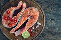 Two fresh raw salmon steaks with spices. Two fresh raw salmon steaks with pepper, chili, salt, lemon and garlic on wooden cutting board on black background Royalty Free Stock Photo