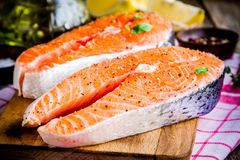 Two fresh raw salmon steaks with peppers. On wooden cutting board Royalty Free Stock Images