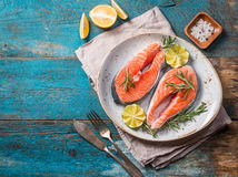 Two fresh raw salmon steaks. In a plate with salt, peppers, lemon, and rosemary on the rustic wooden table, top view Stock Photo