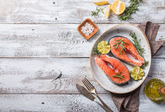 Two fresh raw salmon steaks. In a plate with salt, peppers, lemon, and rosemary on the rustic wooden table, top view Royalty Free Stock Image