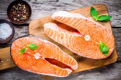 Two fresh raw salmon steaks with salt, peppers, and basil. On the rustic wooden table Royalty Free Stock Photos