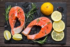 Two fresh raw salmon steaks with salt, peppers, lemon and rosemary with ice cubes on black slate board. Over rustic table. top view Royalty Free Stock Images