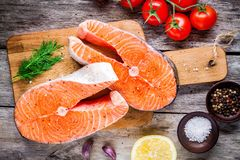 Two fresh raw salmon steaks with salt, peppers, lemon, tomatoes and dill. On the rustic table Stock Photos