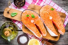 Two fresh raw salmon steaks with salt, peppers, and olive oil Stock Images