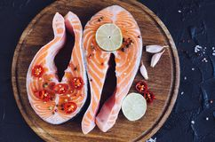 Two fresh raw salmon steaks with spices. Two fresh raw salmon steaks with pepper, chili, salt, lemon and garlic on wooden cutting board on black background Royalty Free Stock Image