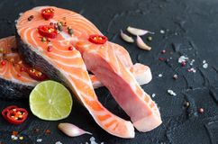 Two fresh raw salmon steaks with spices. Two fresh raw salmon steaks with pepper corns, chili, salt, lemon and garlic on black background. Healthy food, diet Royalty Free Stock Photography
