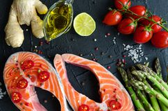 Two fresh raw salmon steaks. With vegetables and spices: asparagus, tomatoes, ginger, pepper corns, salt, pepper chili, lemon and olive oil on black background Royalty Free Stock Images