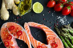 Two fresh raw salmon steaks. With vegetables and spices: asparagus, tomatoes, ginger, pepper corns, salt, pepper chili, lemon and olive oil on black background Royalty Free Stock Photos