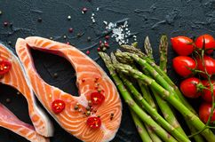 Two fresh raw salmon steaks. With vegetables and spices: asparagus, tomatoes, pepper corns, salt, pepper chili, lemon and olive oil on black background. Healthy Stock Photography