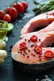Two fresh raw salmon steaks. With vegetables and spices: asparagus, tomatoes, ginger, pepper corns, salt, pepper chili, lemon and olive oil on black background Stock Images