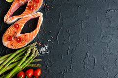 Two fresh raw salmon steaks. With vegetables and spices: asparagus, tomatoes, pepper corns, salt, pepper chili, lemon and olive oil on black background. Healthy Royalty Free Stock Photo