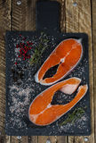 Two fresh raw salmon or trout steaks with salt, peppers and thyme Stock Image