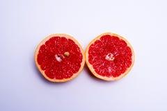 Two fresh red grapefruit halves on white background. Two fresh red grapefruit halves on a white background Stock Photos