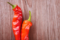 Two fresh red hot chili peppers on a wooden background Stock Photos