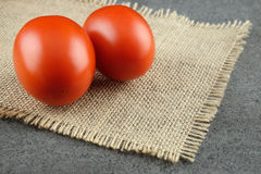 Two fresh red tomatoes on a burlap cloth. Stock Photography