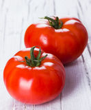 Two fresh red tomatoes. Fresh red tomatoes on wihite wooden background Royalty Free Stock Images