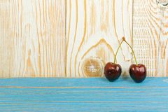 Fresh Overripe ripe Cherries on Blue Rustic Wooden Background. Two fresh ripe cherries on old wooden background for design montage. Blue wood table desk board stock images