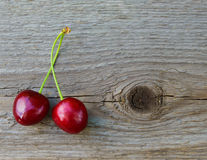 Two Fresh Ripe Red Sweet Cherries on Wooden Background Stock Images