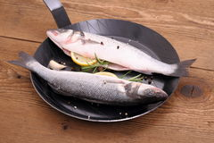 Two fresh sea bass fish on frying pan with lemon Royalty Free Stock Image