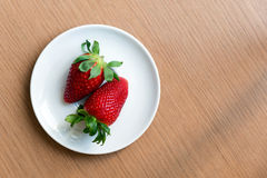 Two fresh strawberries on a white plate, view from above Royalty Free Stock Image