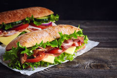 Two fresh submarine sandwiches. With ham, cheese, bacon, tomatoes, lettuce, cucumbers and onions on dark wooden background Royalty Free Stock Photos