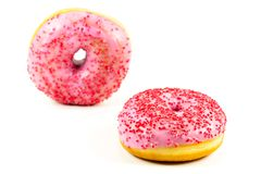 Two fresh sweet pink donut with red sprinkles royalty free stock photos